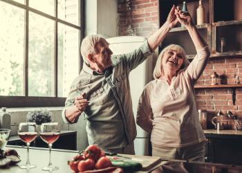 older couple with veneers dancing in kitchen